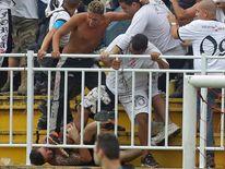 ans of Rio de Janeiro's Vasco da Gama attack a fan of Parana's Atletico PR
