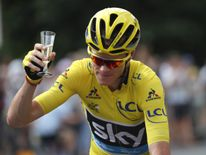 Chris Froome holds a glass of champagne