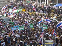 Thai anti-government protesters wave national flags during a rally in Bangkok
