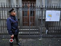 A policeman standing guard outside Saint-Yves des Bretons in Rome after a small explosion nearby.
