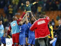 Brazilian players, hold a younger fan aloft at the end of their friendly with South Africa.