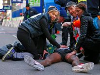 Mo Farah of Great Britain is taken care of by medical personal after he collapsed at the finish line after finishing in second place at the 2014 New York City Half Marathon