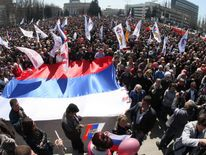Pro-Russian protesters hold Russian national flags during the rally in eastern Ukrainian city of Donetsk