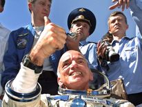 US space tourist Dennis Tito gives a thumb up after landing back on Earth in Kazakhstan