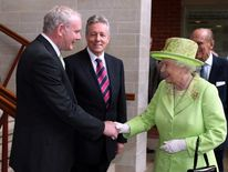 Queen Elizabeth II shakes hands with Northern Ireland Deputy First Minister Martin McGuinness watched by First minister Peter Robinson
