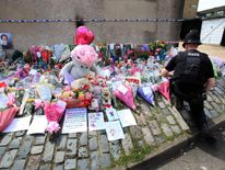 A police officer places some flowers at the makeshift memorial to Tia Sharp