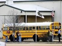 Residents look over the school bus where a shooting occurred near Destiny Church