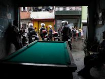 Residents of the Brasilandia favela talk inside a bar as police officers patrol