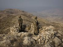 Pakistani soldiers secure an area on top