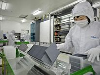 A masked worker in a lab coat sorting silicon wafers