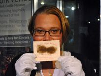 York Castle Museum Curator of History Alison Bodley with a Victorian Valentine's Day card including facial hair to resemble a moustache.