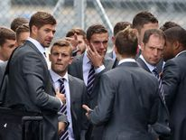 Comedian Simon Brodkin (back to camera), Steven Gerrard (left) Jack Wilshere (second left) and Jordan Henderson.