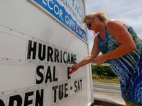 Maryline Epping of Avon, North Carolina finishes the words on a sign out in front of her shop before Hurricane Arthur in Buxton