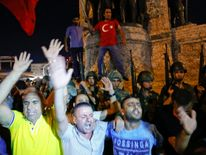 People demonstrate in front of the Republic Monument at the Taksim Square in Istanbul