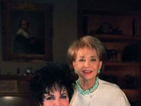 Actress Elizabeth Taylor and broadcaster Barbara Walters pose in Taylor's home during a break in Wal..