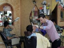 A Palestinian barber shaves the beard of a youth at at his shop in Gaza City