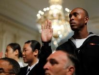 Members of the U.S. military and military spouses recite the Oath of Allegiance to become naturalized U.S. citizens during a ceremony hosted by Obama at the White House in Washington