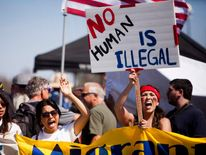 Demonstrators picket before the possible arrival of undocumented migrants who may be processed at the Murrieta Border Patrol Station in Murrieta, California