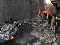 Syrian men inspect the scene of a car bomb explosion in Jaramana, Damascus