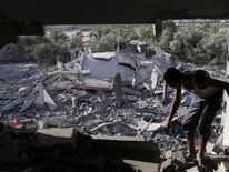A Palestinian inspects a house which police said was damaged in an Israeli air strike that destroyed a neighboring house in Deir El-Balah in the central Gaza Strip