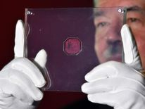 Sotheby's employee examines British Guiana One-Cent Magenta stamp
