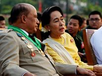Myanmar's opposition leader Aung San Suu Kyi speaks with Deputy Minister for Border Affairs Major General Zaw Win during Armed Forces Day in Naypyitaw