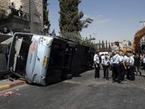 Israeli policemen stand next to an overturned bus after a Palestinian man rammed an excavator into it