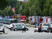 Police and firefighters are seen near a shopping centre in Munich, not far from the city's Olympic Stadium