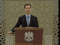 Bashir Al Assad is sworn in as Syria's President for a third term, with a hand on the Koran