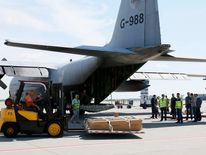 A worker uses a forklift to load coffins containing remains of Malaysia Airlines MH17 victims on to a plane at Kharkiv airport