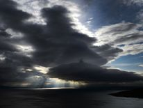 Sunlight makes its way through heavy clouds over Lake Geneva