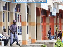 A watchman guards closed shops in Goma