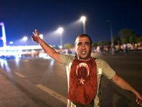A man covered with blood points at the Bosphorus bridge as Turkish military clashes with people at the entrance to the bridge in Istanbul