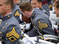 West Point Graduate Fields is comforted after becoming emotional upon receiving his diploma during the commencement ceremony at United States Military Academy at West Point