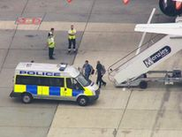 Jeremy Forrest, with head covered, is escorted to a police car after arriving at Gatwick airport by plane.