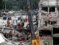 Rescue workers attempt to rescue clothing workers from the rubble of the collapsed Rana Plaza building, in Savar, Bangladesh