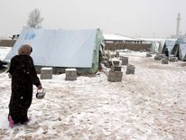 A Syrian refugee woman holds a pot as she walks in snow outside their tents during a winter storm in al-Marj, in the Bekaa valley