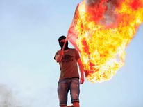 Protester burns a U.S. flag during a demonstration over the capture of senior al Qaeda figure al-Liby by U.S. authorities, in Benghazi