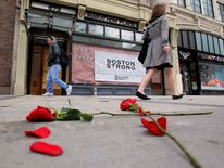 Flowers lay on the sidewalk at the site of the first explosion as people walk along Boylston Street in Boston