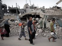 A Palestinian family flees their destroyed neighbourhood to take shelter in a United Nations school
