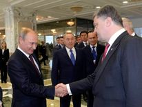 Russian President Vladimir Putin shakes hands with his Ukrainian counterpart Petro Poroshenko in Minsk