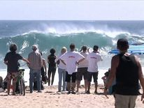 Californians watch the waves coming onto the beach