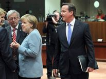 David Cameron walks past Jose Manuel Barroso, Helle Thorning-Schmidt, Jean-Claude Juncker and Angela Merkel