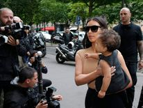 TV personality Kim Kardashian holds her baby in her arms as she shops in Paris