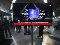 "An information screen displays a message ""Let Us Pray For Flight MH370"", regarding the missing Malaysia Airlines flight, at Kuala Lumpur International Airport in Sepang"