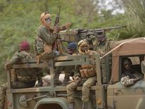Malian soldiers patrol aboard a vehicule mounted with a machine gun in a street of Diabaly