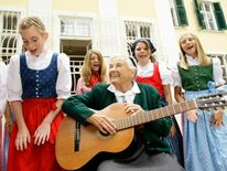 Maria von Trapp makes plays guitar and sings with children in front her former home Villa Trapp in Salzburg