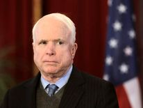 U.S. senator John McCain listenss during a news conference in Riga