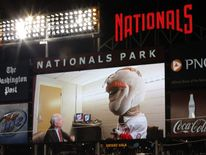 U.S. Senator John McCain (R-AZ) (L) gives a pep talk to Washington Nationals mascot Teddy Roosevelt