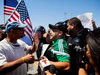 Singer Rivera who is picketing for the migrants joins other demonstrators as they shout against those picketing against the arrival of undocumented migrants who were scheduled to be processed at the Murrieta Border Patrol Station in California